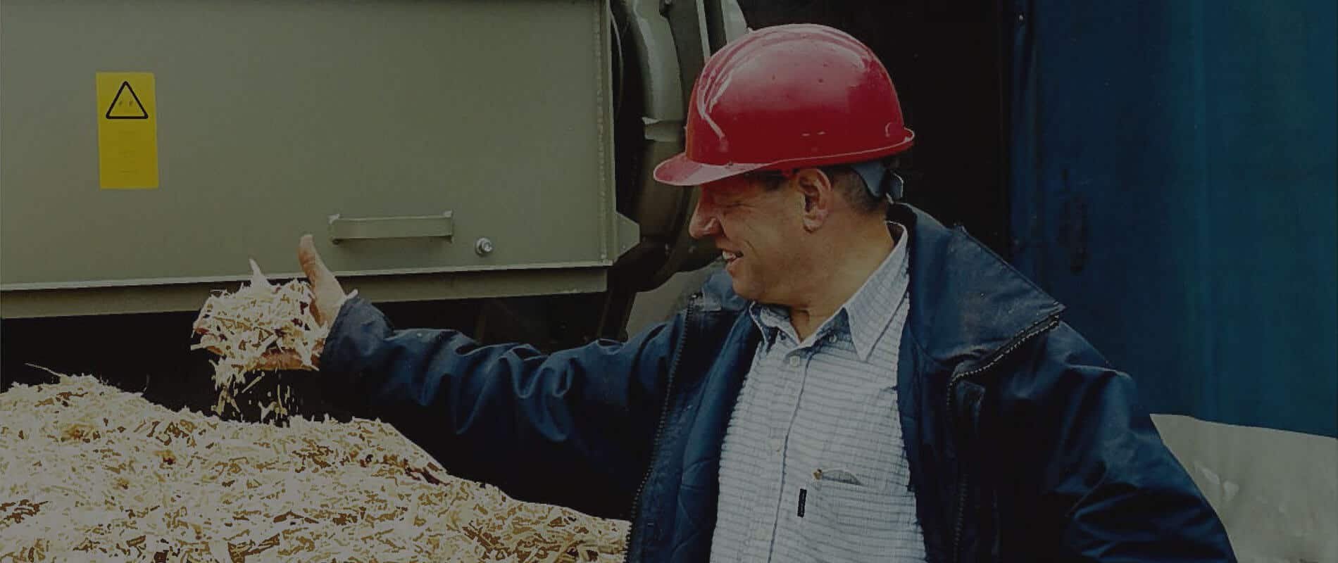 Man holding wood chips in his hand smiling with Scanhugger wood shredder in background