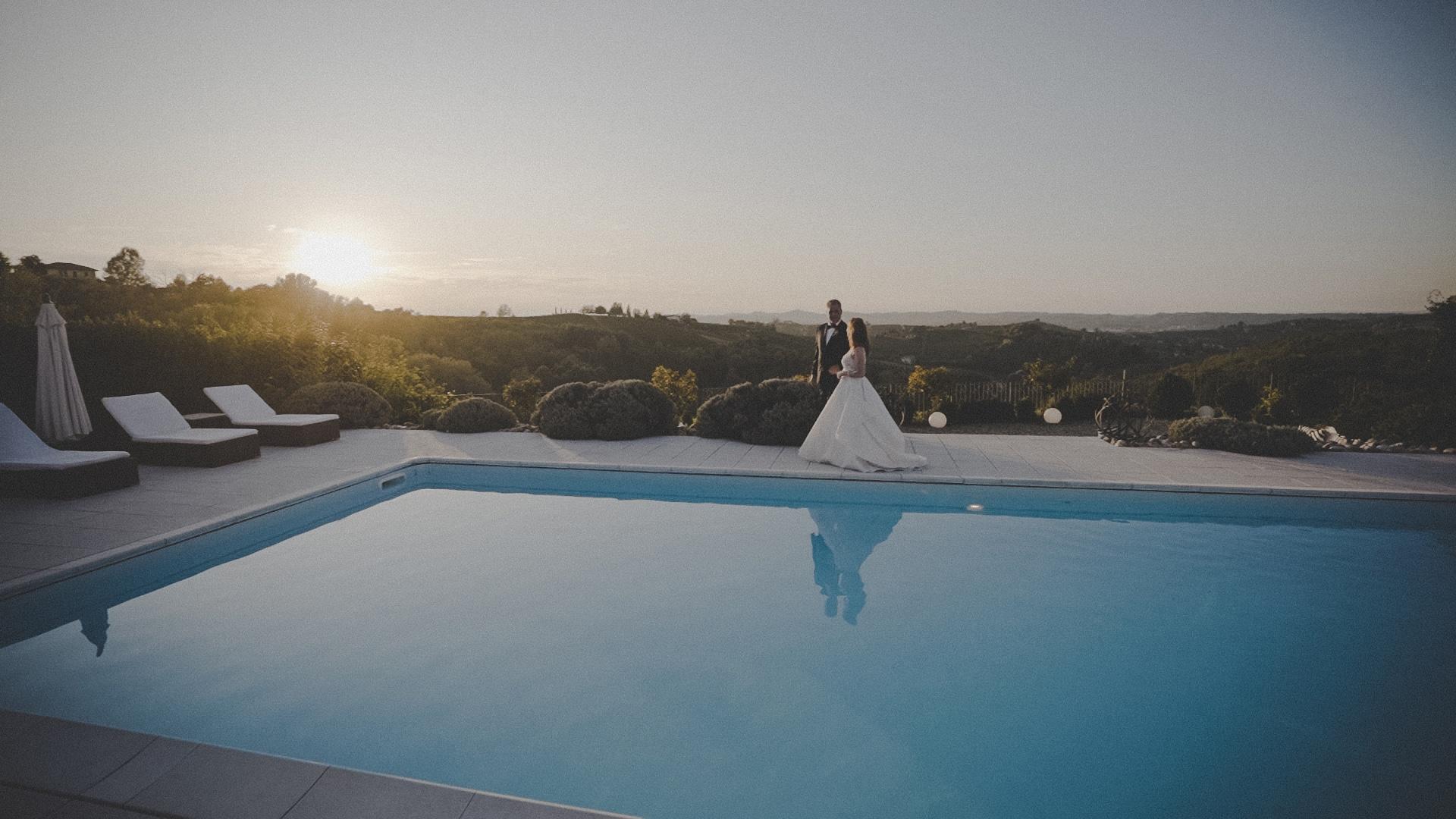 sposi al tramonto sul bordo di una piscina