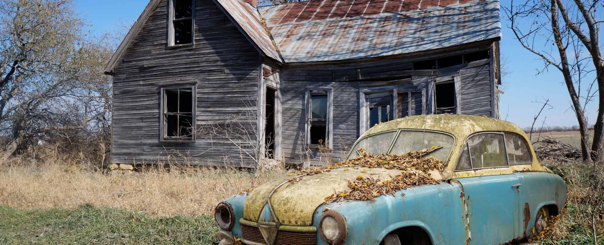 Rusted old car in the grass in front of a dilapidated house