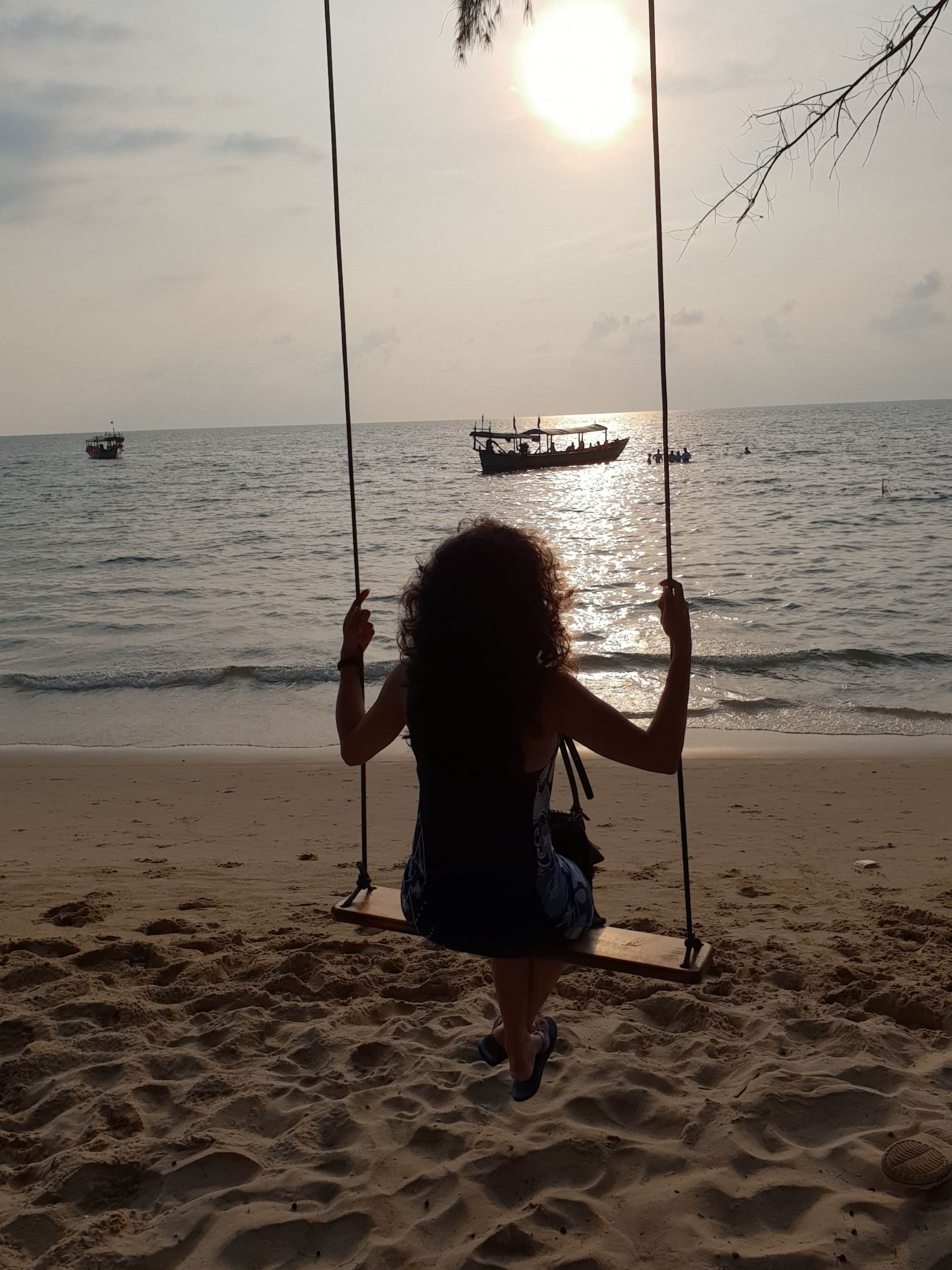 Girl on Swing at a beach watching the sun