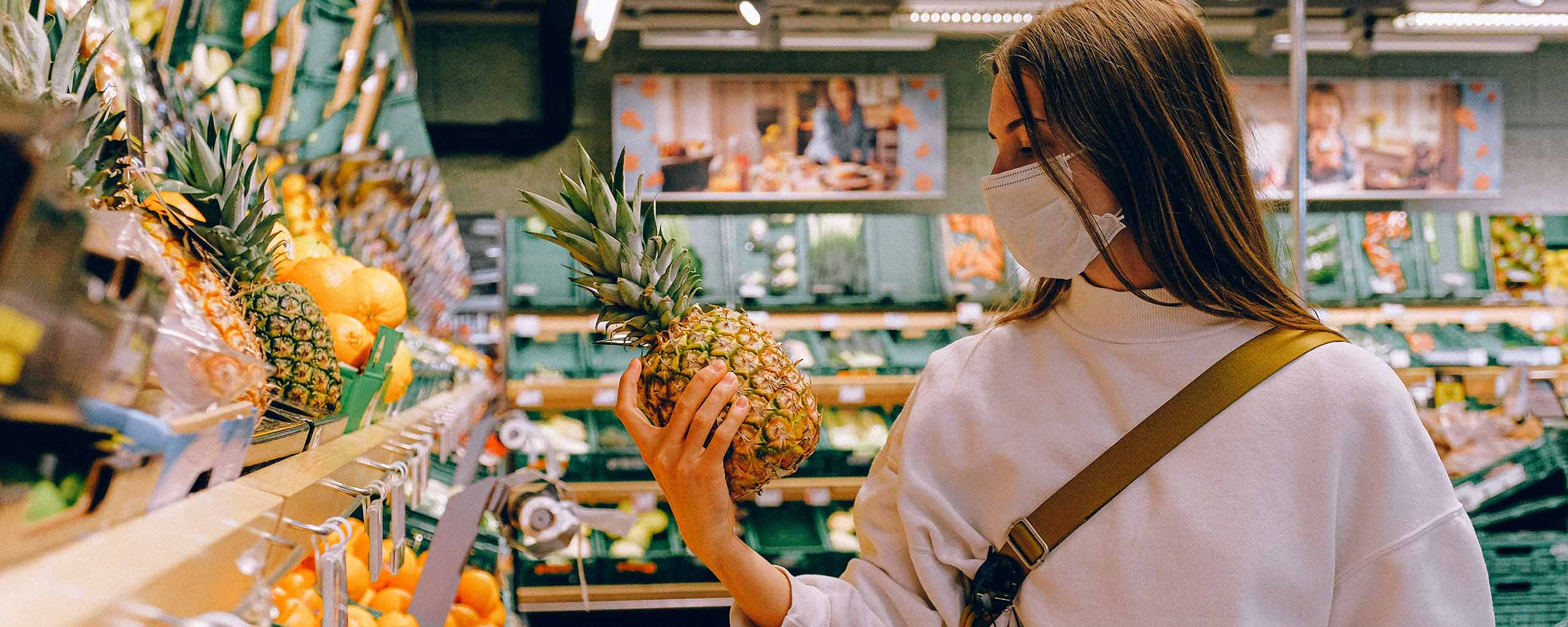 Woman shopping at the grocery store wearing a facemask and holding a pineapple
