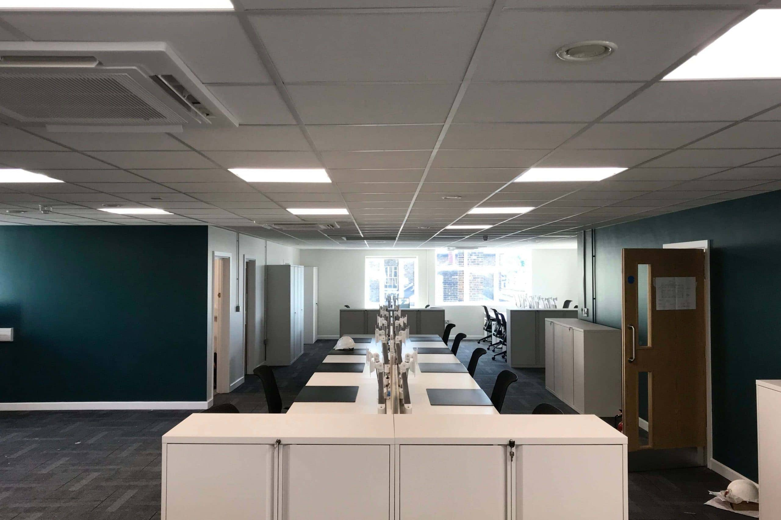 Norwood junction large commercial air conditioning solution by SubCool FM white cassette units in ceiling of office desk space