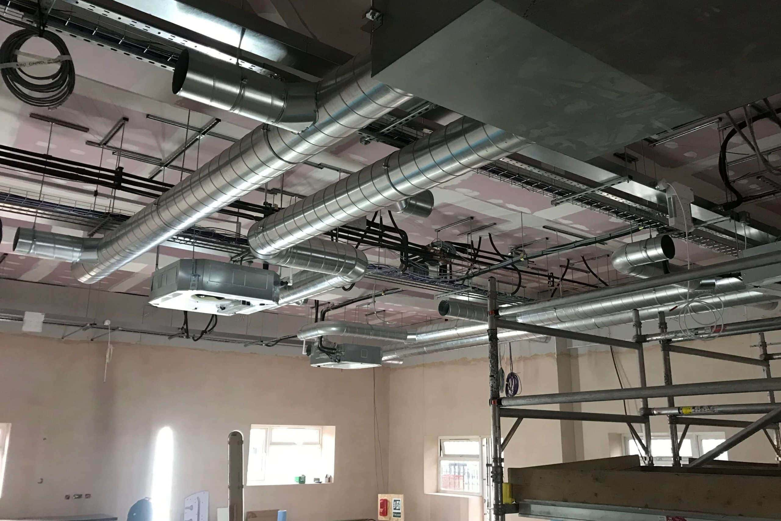 Norwood junction large commercial air conditioning solution by SubCool FM hanging unit amongst pipes in ceiling building view