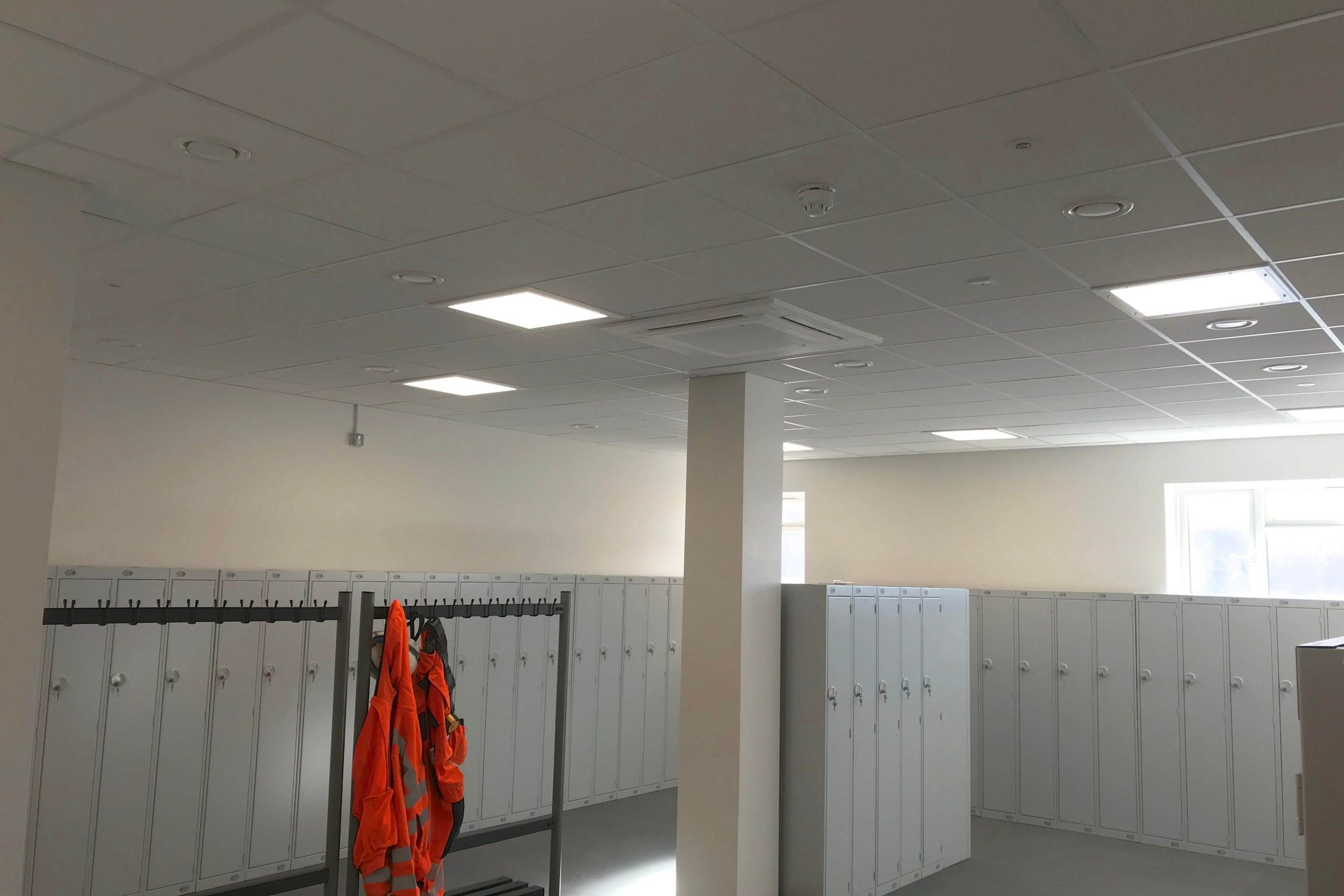 Norwood junction large commercial air conditioning solution by SubCool FM white ceiling cassette unit in locker room