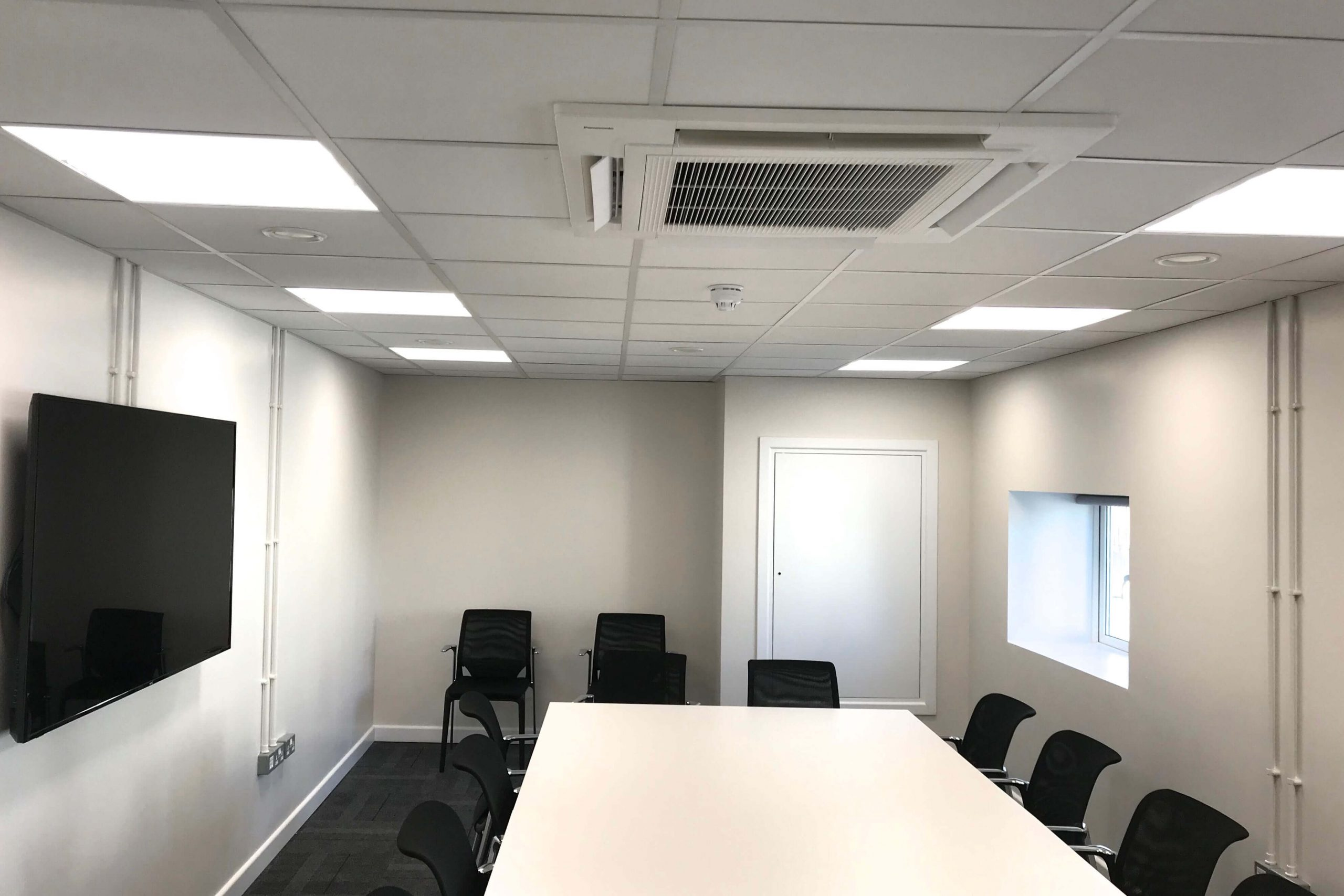 Norwood junction large commercial air conditioning solution by SubCool FM white cassette ceiling unit in meeting room