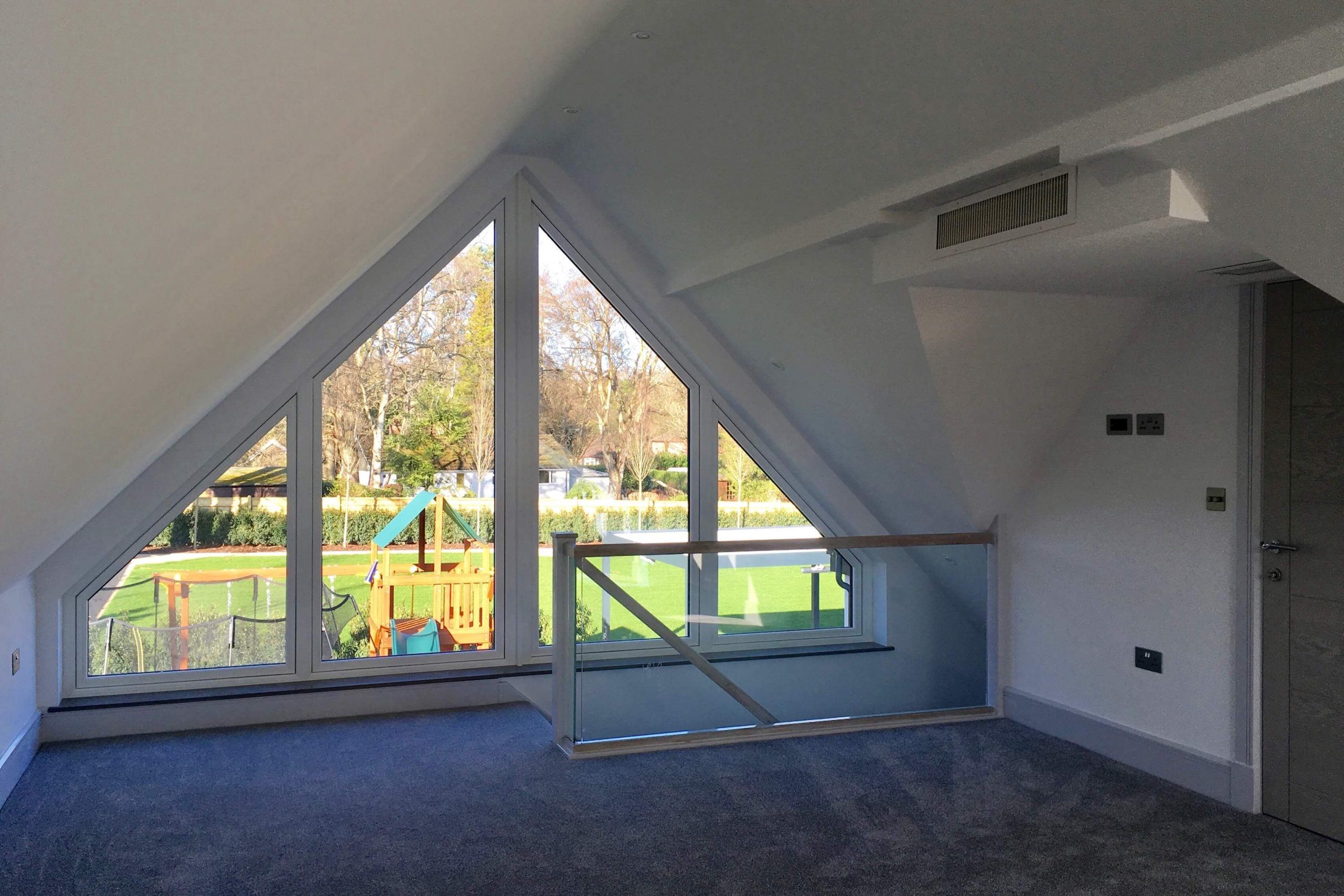 Scandia Hus new build project upstairs bedroom overlooking garden with 2 air grills by door as part of MVHR and air conditioning system by SubCool FM