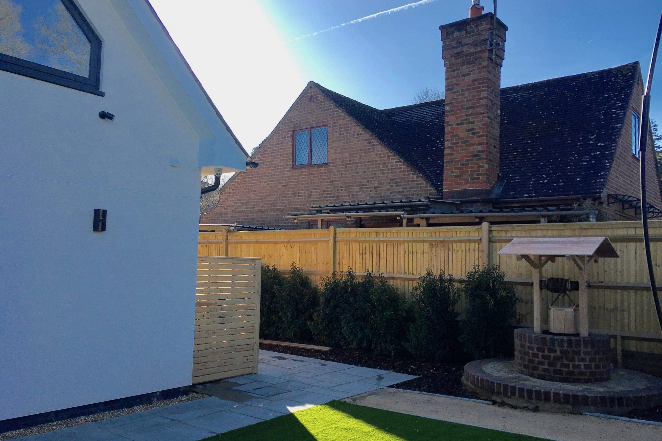 Outdoor MVHR & aircon units in discreet wooden area at domestic build side view