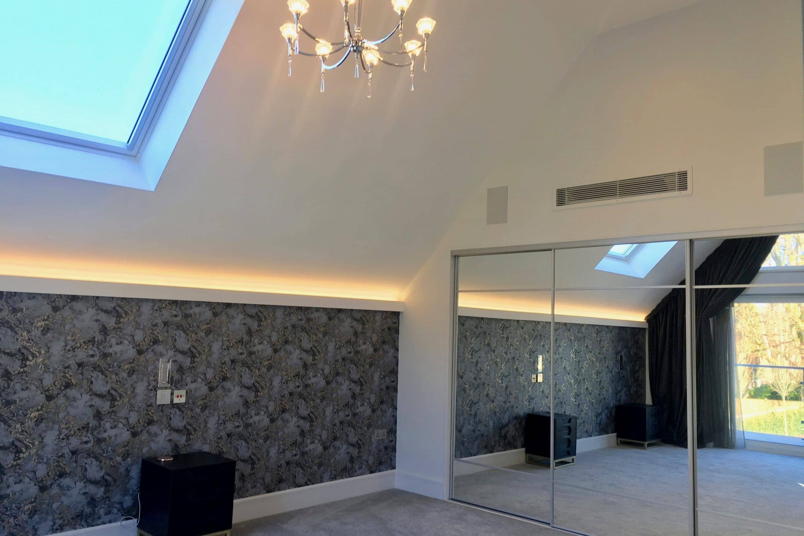 Master bedroom in Scandia Hus new build with air conditioning and MVHR system above and within wardrobe designed and fitted by SubCool FM
