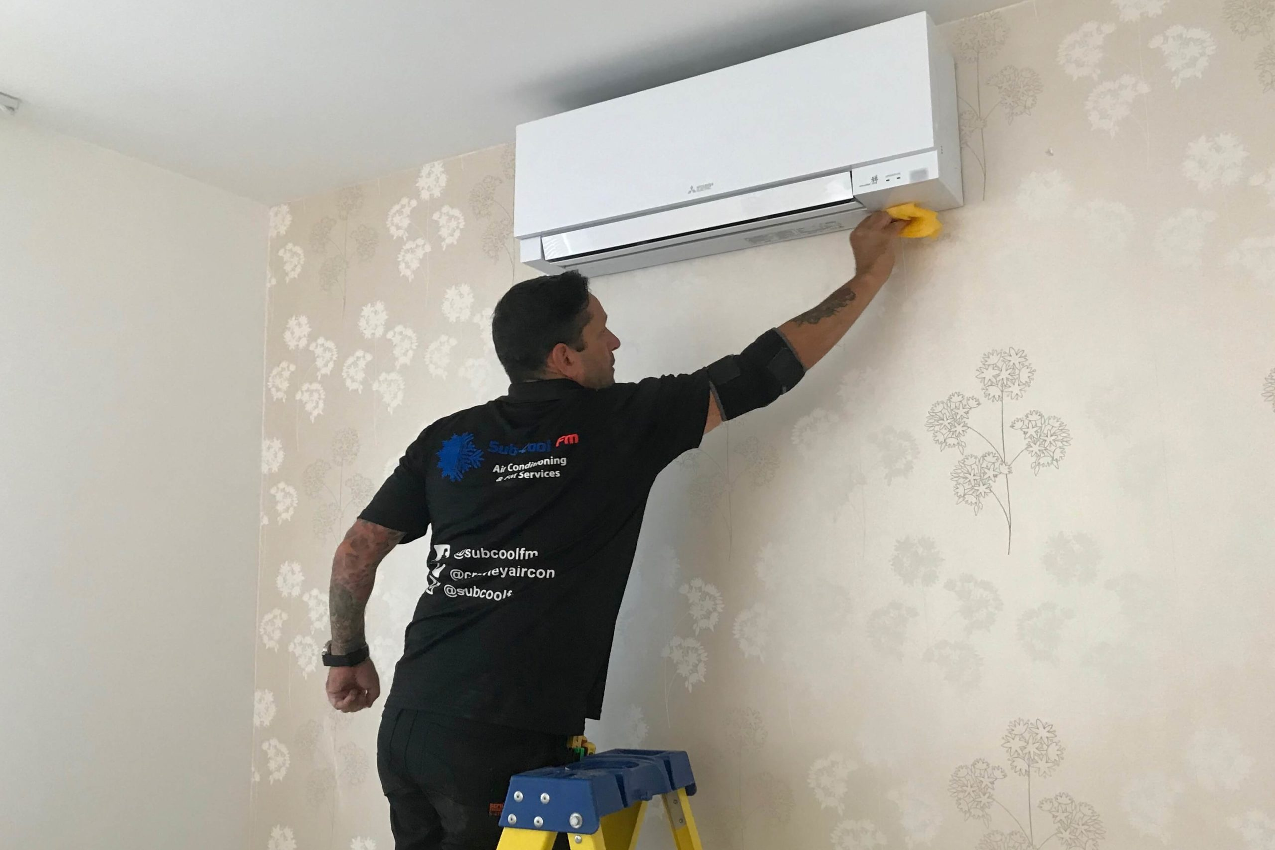 SubCool FM engineer working on white Mitsubishi Electric wall mounted air conditioning unit