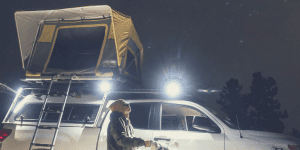 A man with standing in front of a truck with a tent on top of it during the night