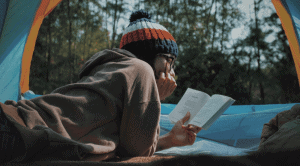 girl reading a book in her tent