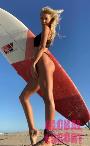 sexy escort blonde posing on the beach with a surfboard