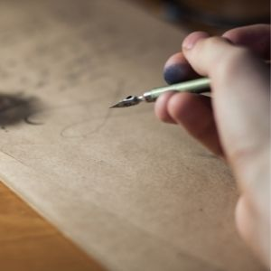 Person writing with old fashioned pen on parchment