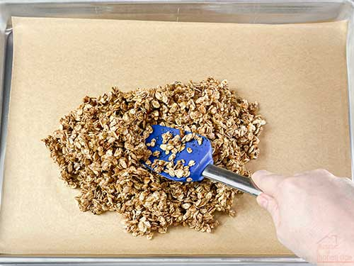 spreading granola in a pan