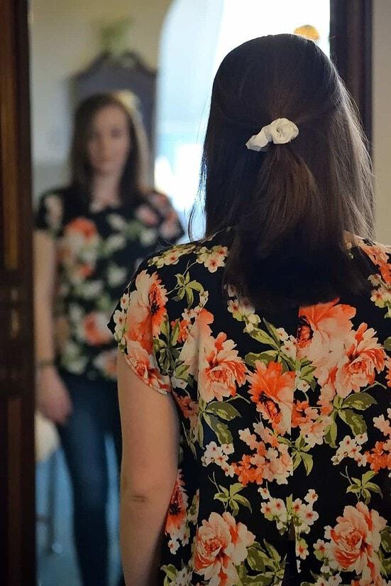 woman looking at self in full length mirror