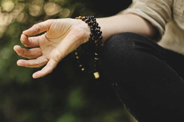 close up of persons hand while meditating with mala beads