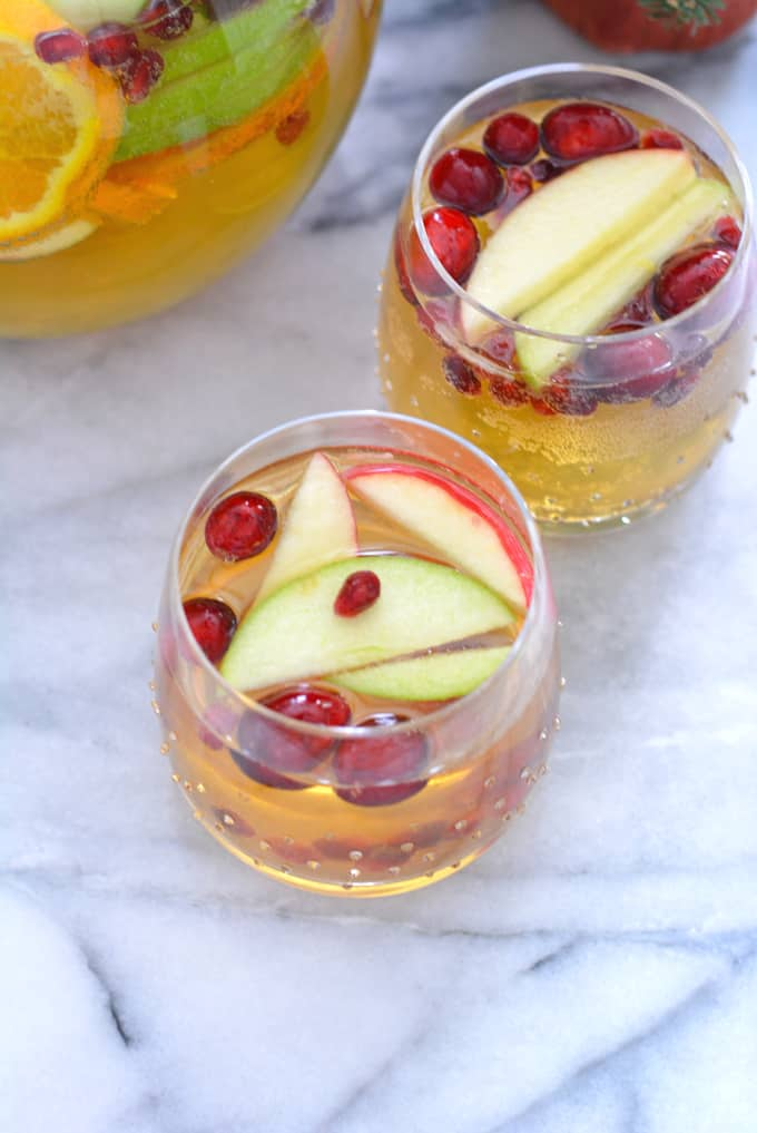 A glass of apple cider sangria topped with apples.