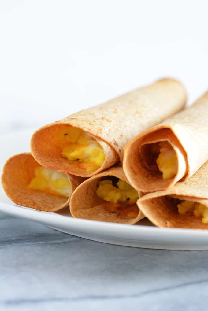 Breakfast taquitos filled with eggs, ham and cheese stacked on a white plate.