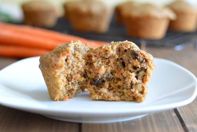 A carrot muffin cut in half sitting on a white plate.