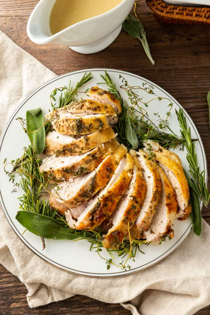 Sliced Bone-In Turkey Breast with Fresh Herbs on a platter