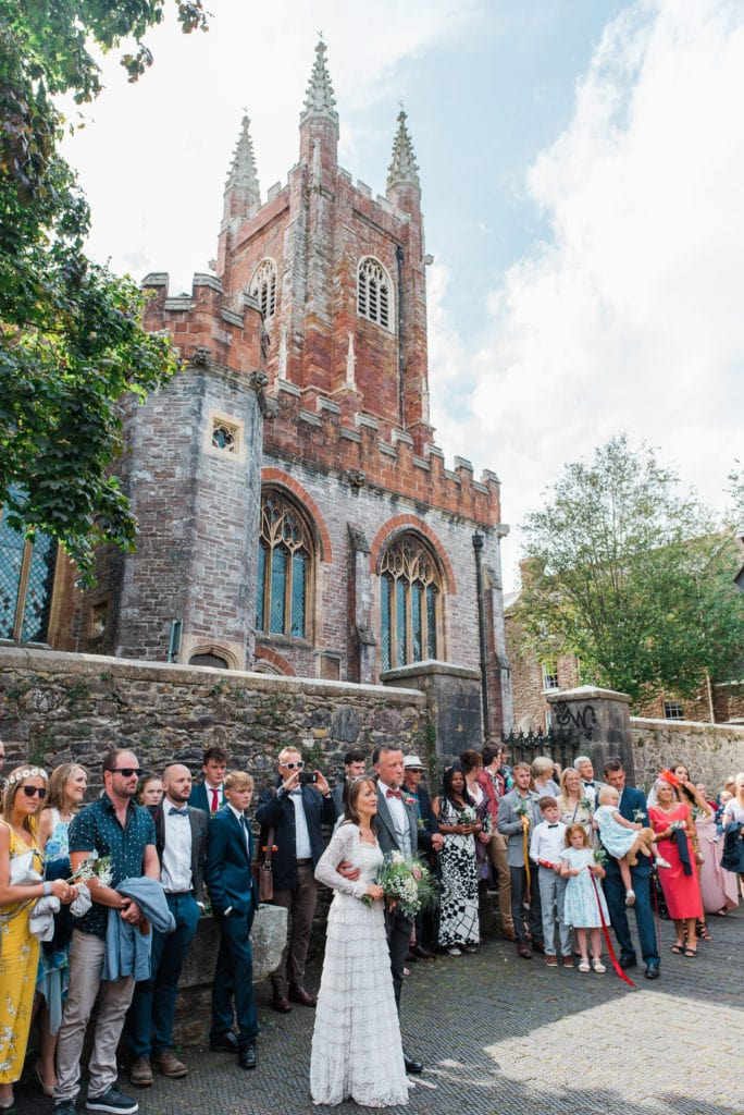 Wedding guests listen to choir outside Totnes Guildhall