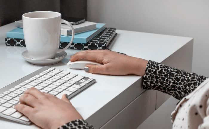 woman using keyboard at white desk