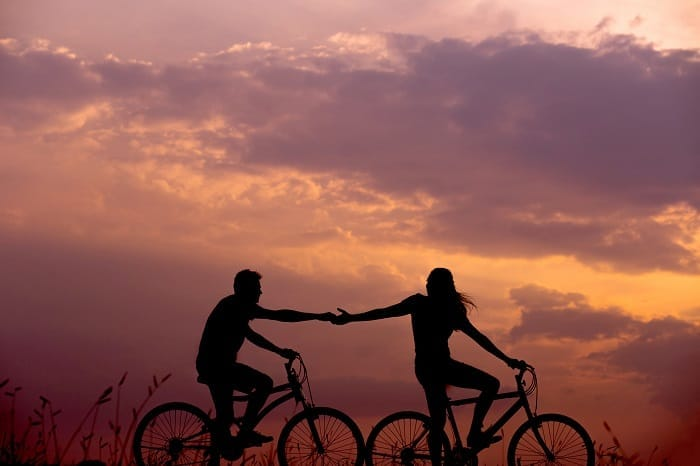 couple holding hands bikes