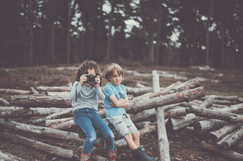 children with a camera in the woods