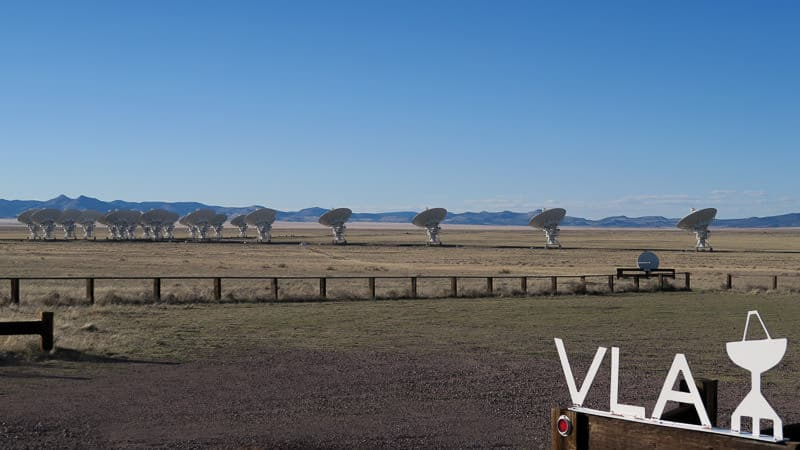 Looking out on the field where the satellites are with the VLA sign in the foreground