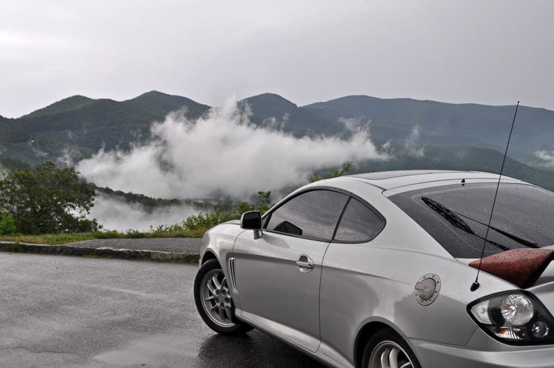 Buddy's old Hyundai Tiburon on the blue ridge parkway in North Carolina with clouds off in the distance