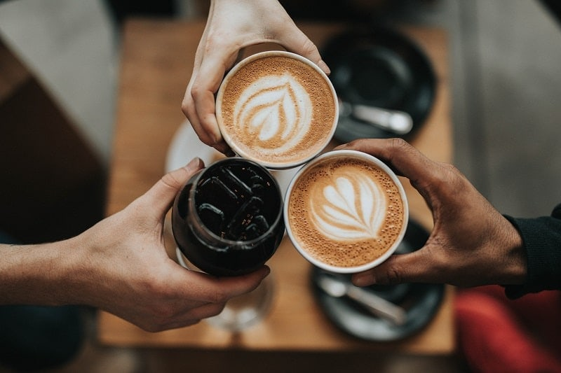 friends with coffees at cafe