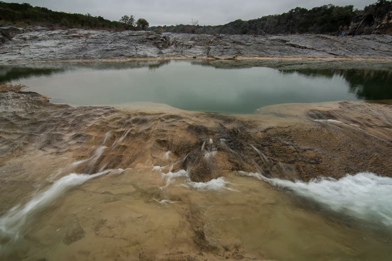 Water flowing over limestone into a larger lake in Pedernales Falls State Park