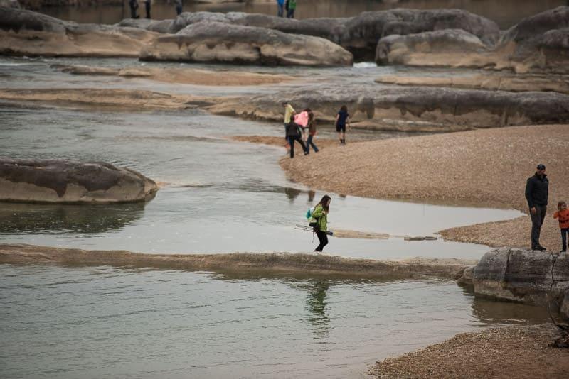 People walking around the waters edge and exploring Pedernales River