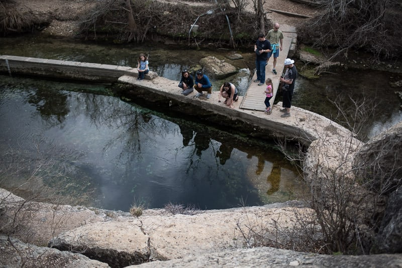 Many tourists looking into Jacob's Well from the viewing platform