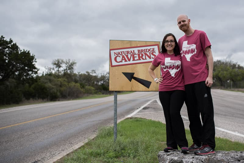 Brooke and buddy in their t-shirts posing by the natural bridge caverns in Texas sign