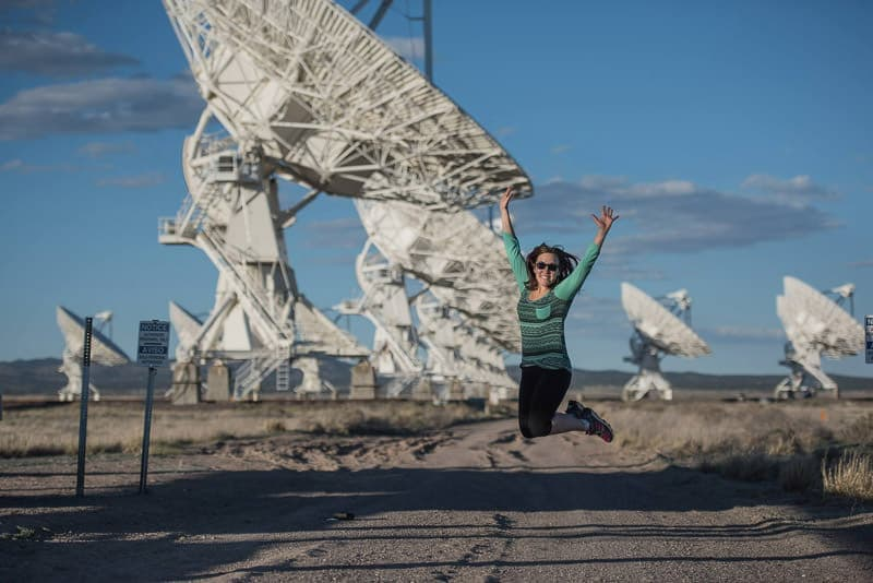 Brooke jumping for joy in front of the huge satellites at the very large array, new mexico