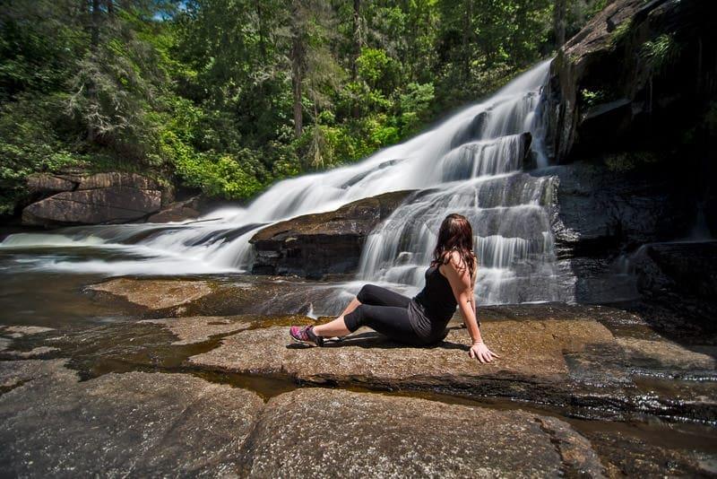Brooke sitting on rocks at the base of triple falls in north carolina