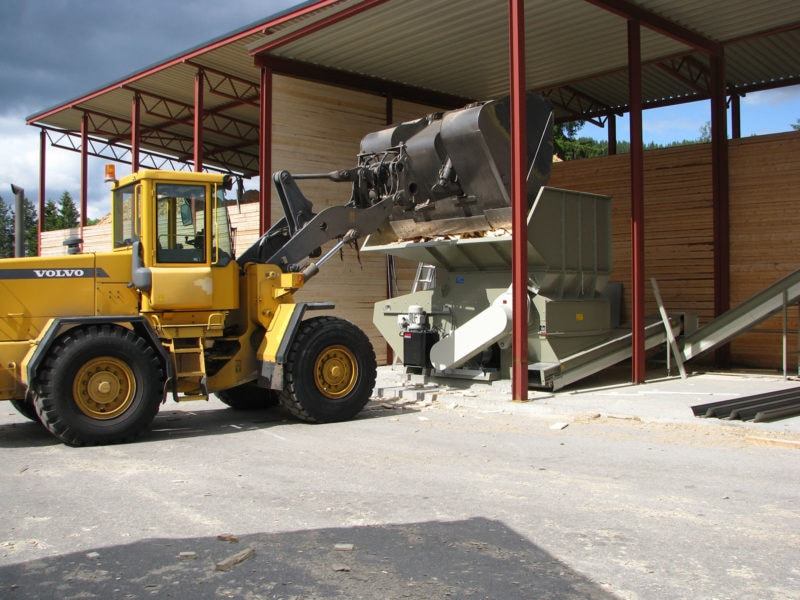 Volvo Tractor Feeding Waste Wood Into Hopper Shredder With Band Conveyors