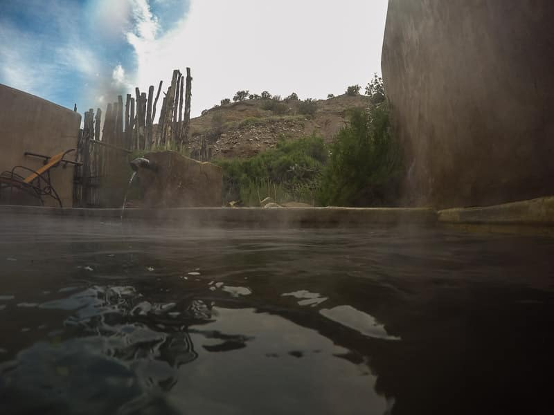 Private Pool at Ojo Caliente with athe cliffs in the bacground and steam coming off the warm water