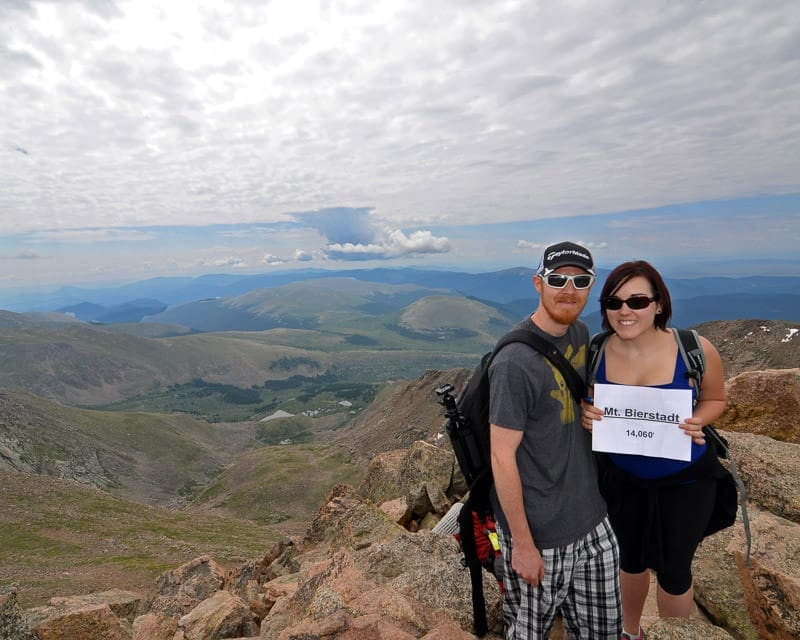 Brooke and Buddy posing with a sign at the top of mt. bierstadt in Colorado