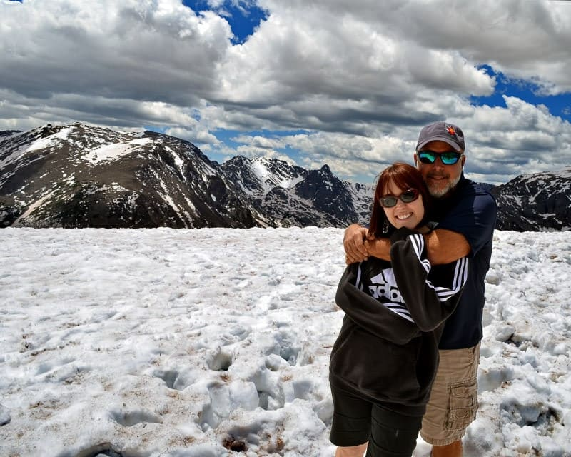 Brooke and her dad on trail ridge road   in colorado with snow on the ground and a beautiful blue sky