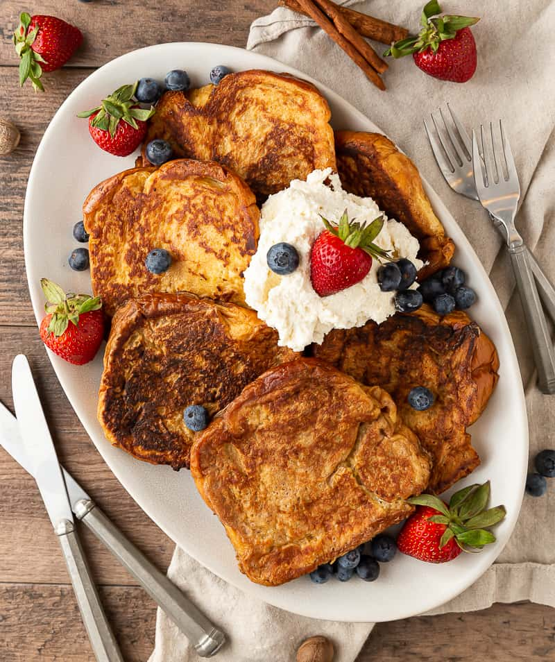plate of french toast with berries and whipped cream