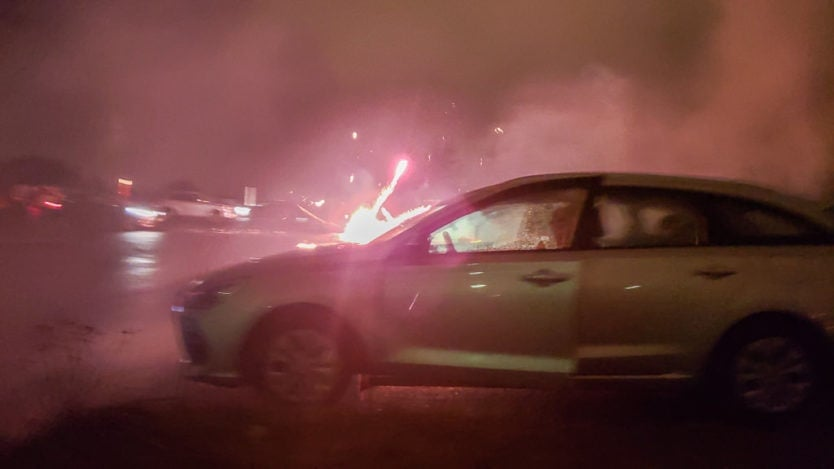fireworks being shot off near car in parking lot at perlan on new year's eve