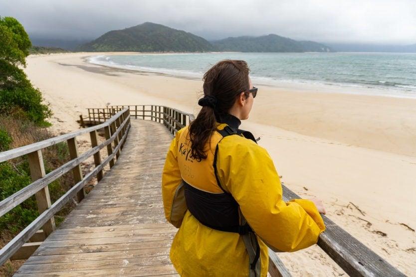 girl looking out into awaroa bay from a walkway on awaroa beach in abel tasman