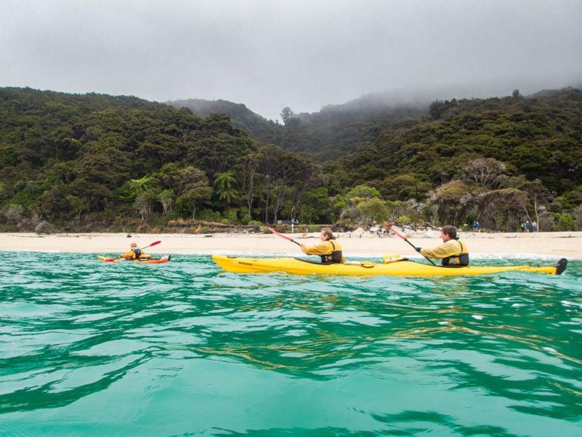 kayakers paddling along the coast of Onetahuti Bay