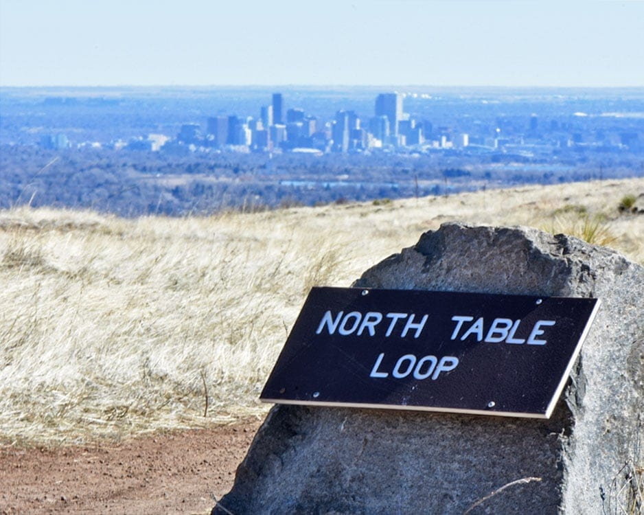 North Table Loop sign with the Denver city line in the background.