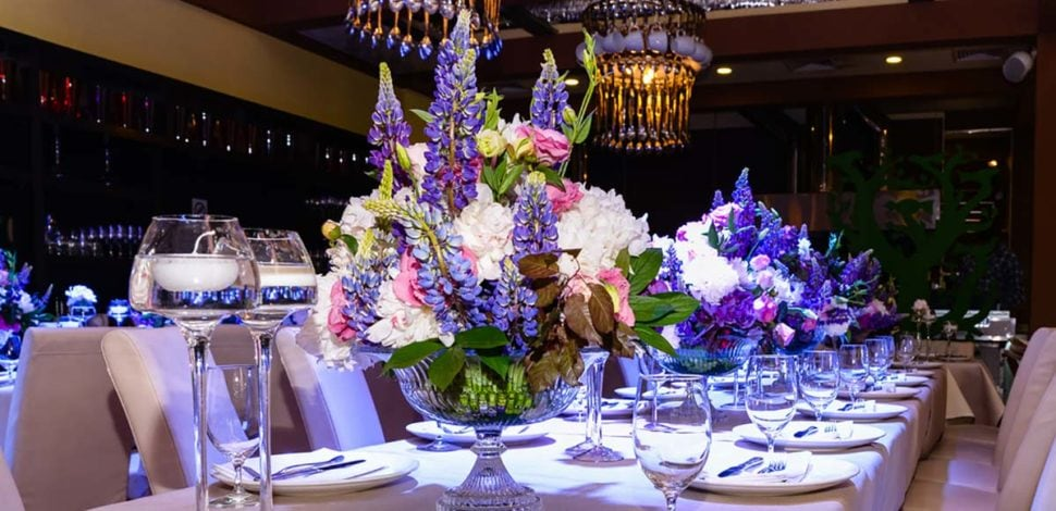Floral centerpiece of purple, pink and white flowers on a long table. Flowers by Marco Island Flowers.