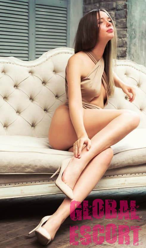 sexy brown-haired woman in beige lingerie sitting on a beige sofa
