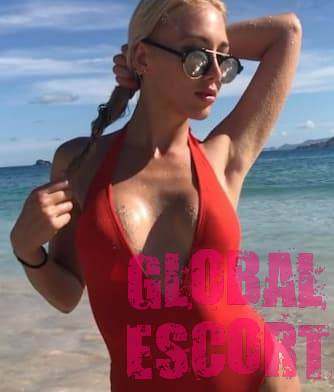 sexy escort blonde posing on the beach in a bright red swimsuit and black glasses