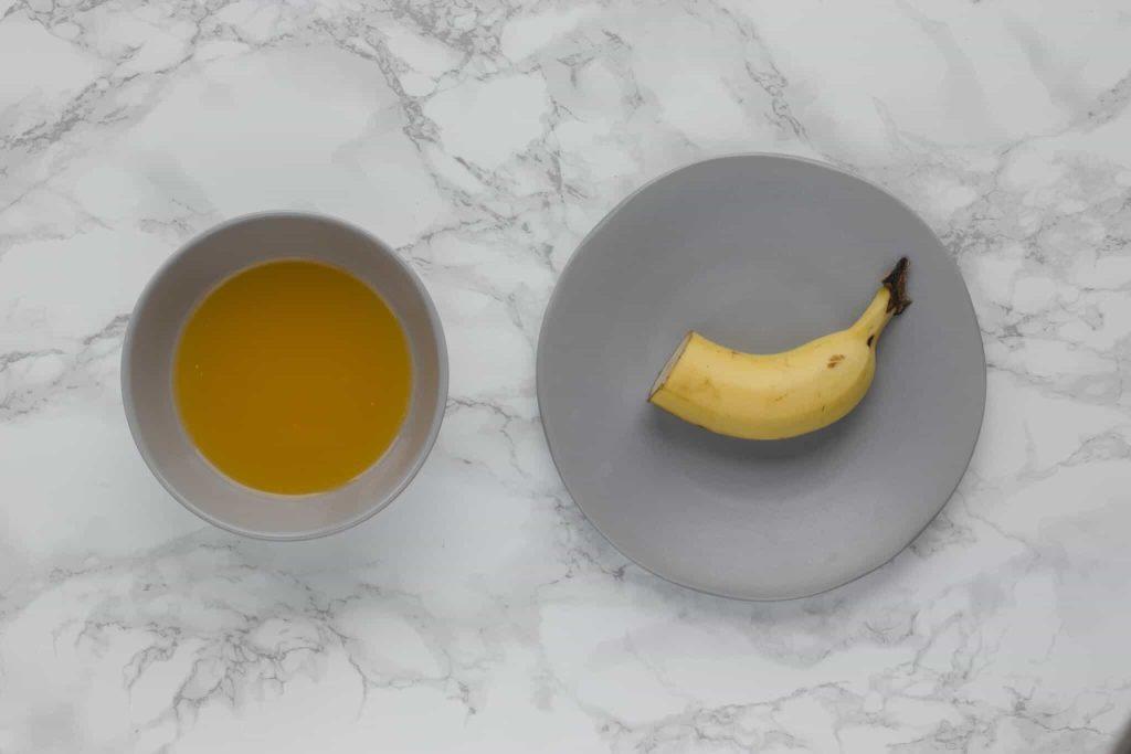 A cut banana alongside a bowl of fruit juice